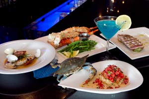 A live blue crab crawls up to say hello to a crabcake of his fallen brothers, surrounded by pan-seared red snapper, Alaskan king crab, jumbo snow crab claws, and an Electric Blue Martini. Tony Robles