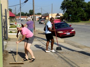 Above: Nicole Foster and Jay Johnson sweep the sidewalk during a neighborhood cleanup on Race Street.  Lisa Maria Garza