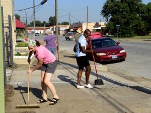 Above: Nicole Foster and Jay Johnson sweep the sidewalk during a neighborhood cleanup on Race Street.  Lisa Maria Garza