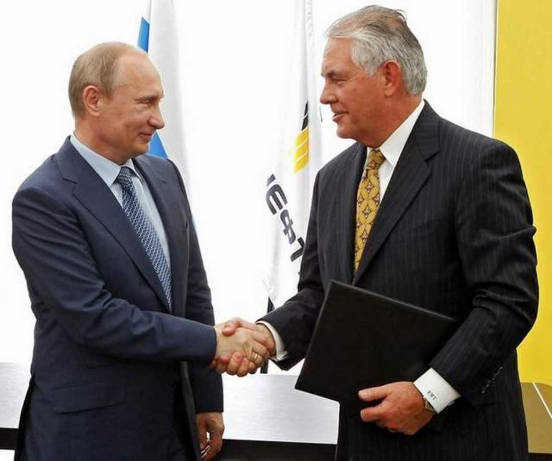 ExxonMobil CEO Rex Tillerson (right) shakes hands with Russian President Vladimir Putin