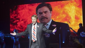 "Will Ferrell poses in front of a negative ad aimed at Zach Galifianakis in ""The Campaign."""