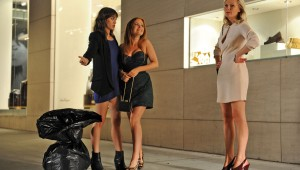 "Lizzy Caplan, Isla Fisher, and Kirsten Dunst tote a trash bag holding a ripped wedding dress around the streets of Manhattan in ""Bachelorette."""