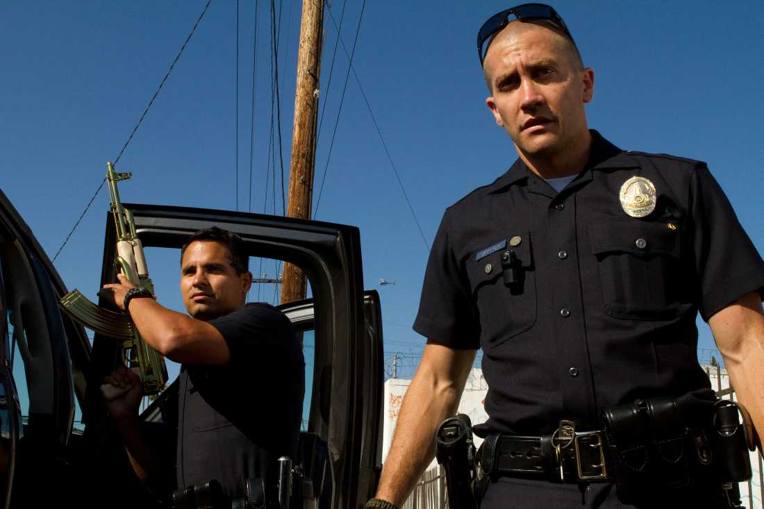 "Michael Peña and Jake Gyllenhaal show off a gold-plated AK-47 in ""End of Watch""."