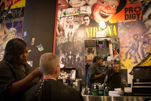 Monica Taylor cuts a customer's hair at Floyd's 99 Barbershop in Montgomery Plaza, surrounded by musical memorabilia. Chase Martinez