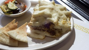 Mixed veggies and pita bread accompany a serving of pastitsio at The Vine. Chase Martinez