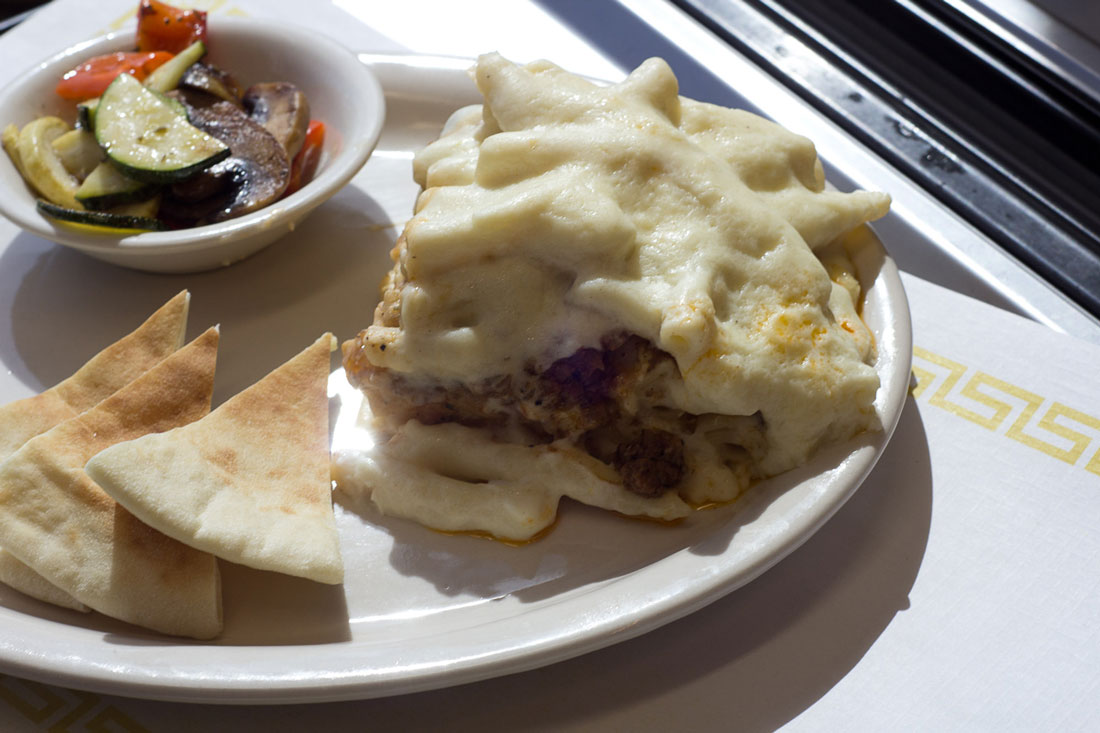 Mixed veggies and pita bread accompany a serving of pastitsio at The Vine. Chase Martinez