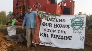 Sam Avery (left) is locked to a tree-cutter at the tar sands blockade, while Gary Stuard holds a protest banner. Coutesy Tar Sands Blockade