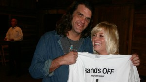 "SCOTT COPELAND AND GIRLFRIEND CAROL PATE CHECK OUT A PROMOTIONAL T-SHIRT AT LAST NIGHT'S SCREENING OF ""THE TEXAS MUSIC HOUR WITH BRAD HINES."""