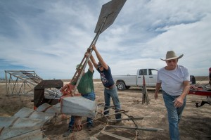 Tommy Houston (right) and helpers erect a windmill to pump water on his ranch in Erath County.