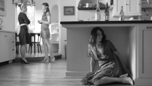 Amy Acker (under counter) hides from her friends' conversation about her love life in Much Ado About Nothing.
