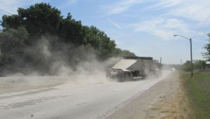 Another truck raises another cloud of dust on East First Street. Mike Phipps