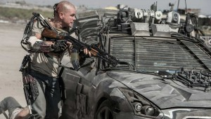 Matt Damon takes cover behind a military vehicle (and his metal exoskeleton) in Elysium.