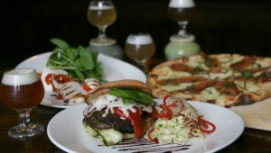 Along with a flight of house beers, Zio Carlo offers a mozzarella caprese appetizer (left), a portobello melt with pasta salad, and a scrumptious brie-and-speck pizza.