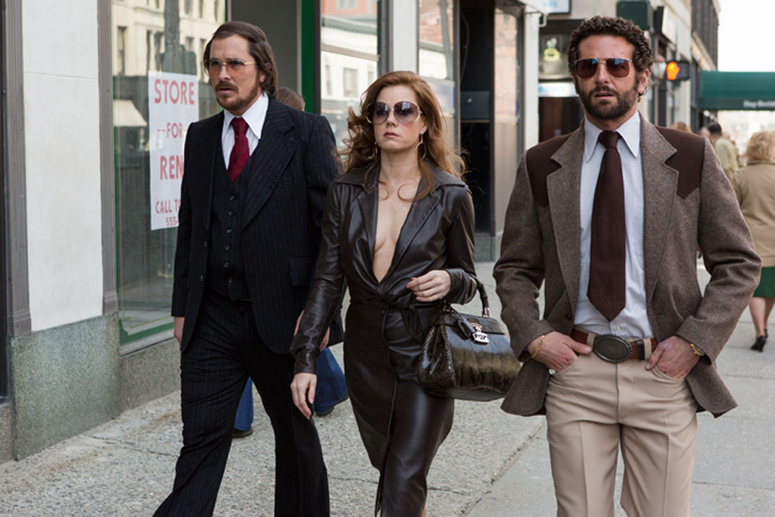 Christian Bale, Amy Adams, and Bradley Cooper are dressed for a con game in American Hustle.