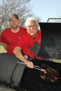 Owner Mike Fisher (right) and assistant pit master Donald Phillips pull some brisket off the fire. Lee Chastain