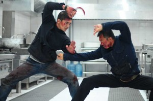 Iko Uwais and Cecep Arif Rahman go at each other with curved blades in a restaurant kitchen in The Raid 2.