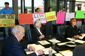 Protesters supporting Kelleher filled the board room while Vic Henderson (left), Marty Leonard, and Mary Kelleher discuss the censure.