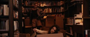 Gaby Hoffmann (standing) tries to cheer up a disconsolate Jenny Slate (in box) in Obvious Child.