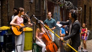 Backed by session musicians and neighborhood kids, Keira Knightley and Mark Ruffalo prepare to record outdoors in Begin Again.