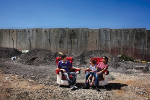 Two furniture makers in the West Bank take a break in chairs they have made.