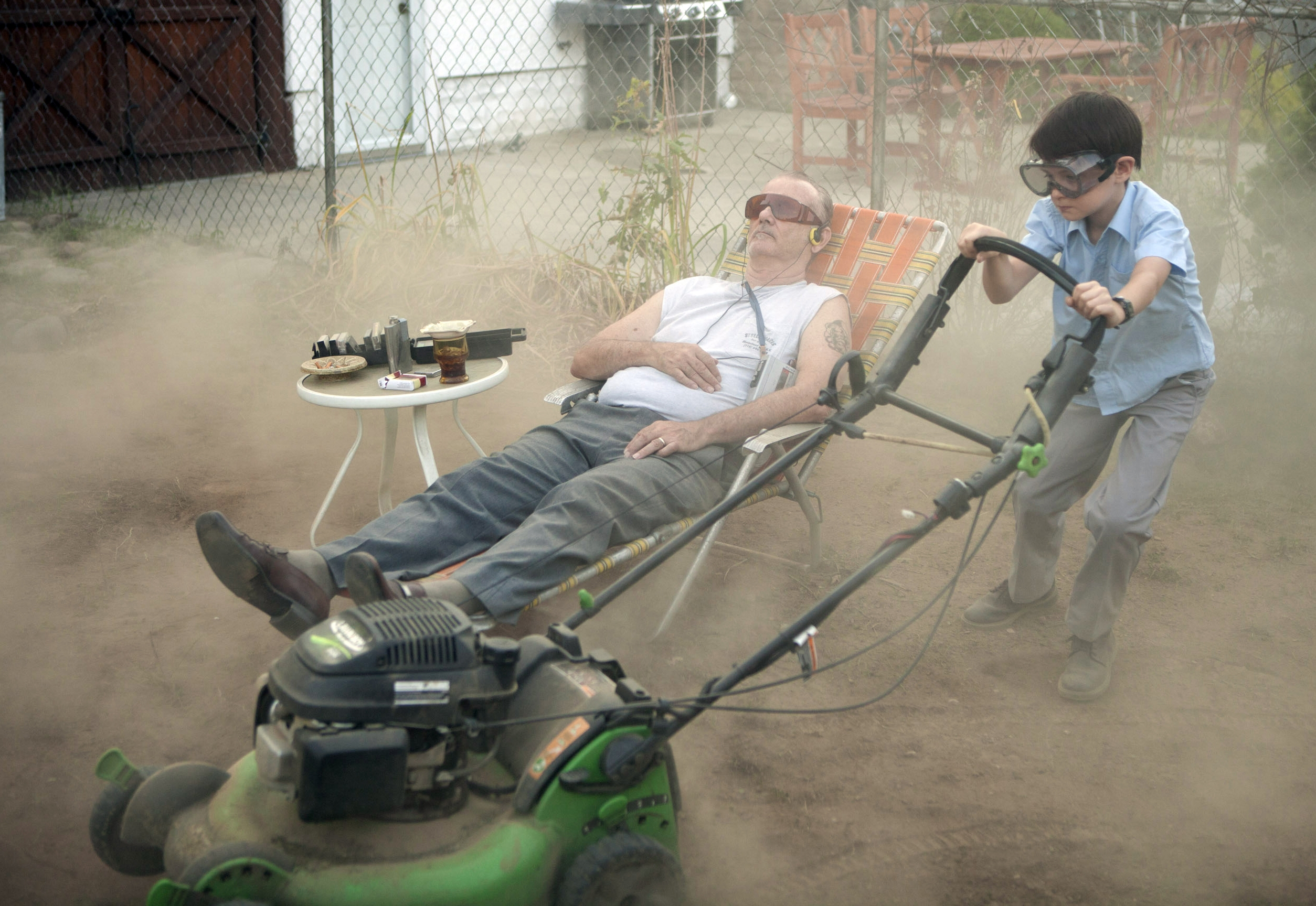 Bill Murray relaxes while Jaeden Lieberher mows his lawn in St. Vincent.