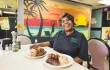 "Owner Maureen ""Angela"" Hucey proudly offers her jerk chicken with steamed cabbage."