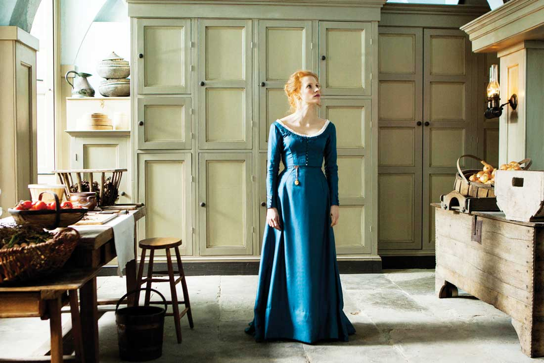 Jessica Chastain wanders the kitchen area in Miss Julie.