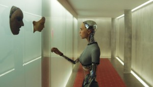 Alicia Vikander ponders the faces of the prototypes before her in Ex Machina.