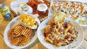 The Trinity River Tap House serves (clockwise from top left) a chicken Acapulco wrap, Baja fish tacos, baked rigatoni with blackened shrimp, and a mac dog. Photo by Brian Hutson.