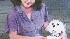 Christina Cranshaw pets a fake dog in Hip Pocket Theatre's Lili.
