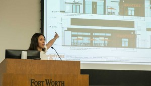 Sasha Camacho points to designs for a Hooters slated for downtown Fort Worth. Photo by Brian Hutson.
