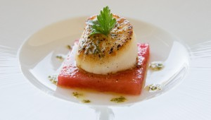 A perfect scallop St. Jaques sits on a slice of watermelon. (Courtesy of Farrar Food Photography).