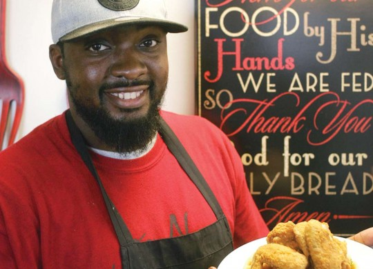 Co-owner Demarcus Davis serves one of Taste N See's signature chicken and waffle dishes. Photo by Lee Chastain.