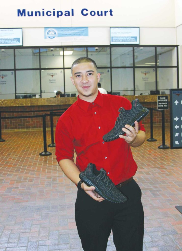 Ryan Perez holds the fake Yeezys after being awarded all of the sneakers in a property hearing. Photo by Jeff Prince.