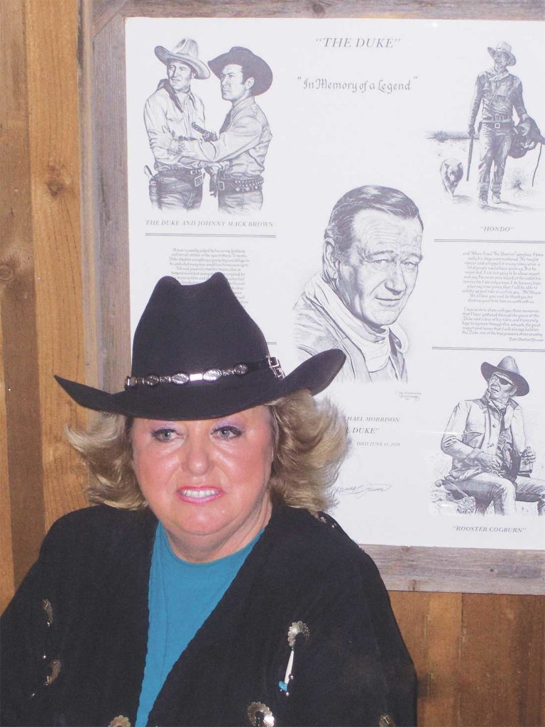 Arnold loved anything to do with the West, including Western movie star John Wayne, shown behind her on a poster that hung on her wall. Photo by Jef Prince.