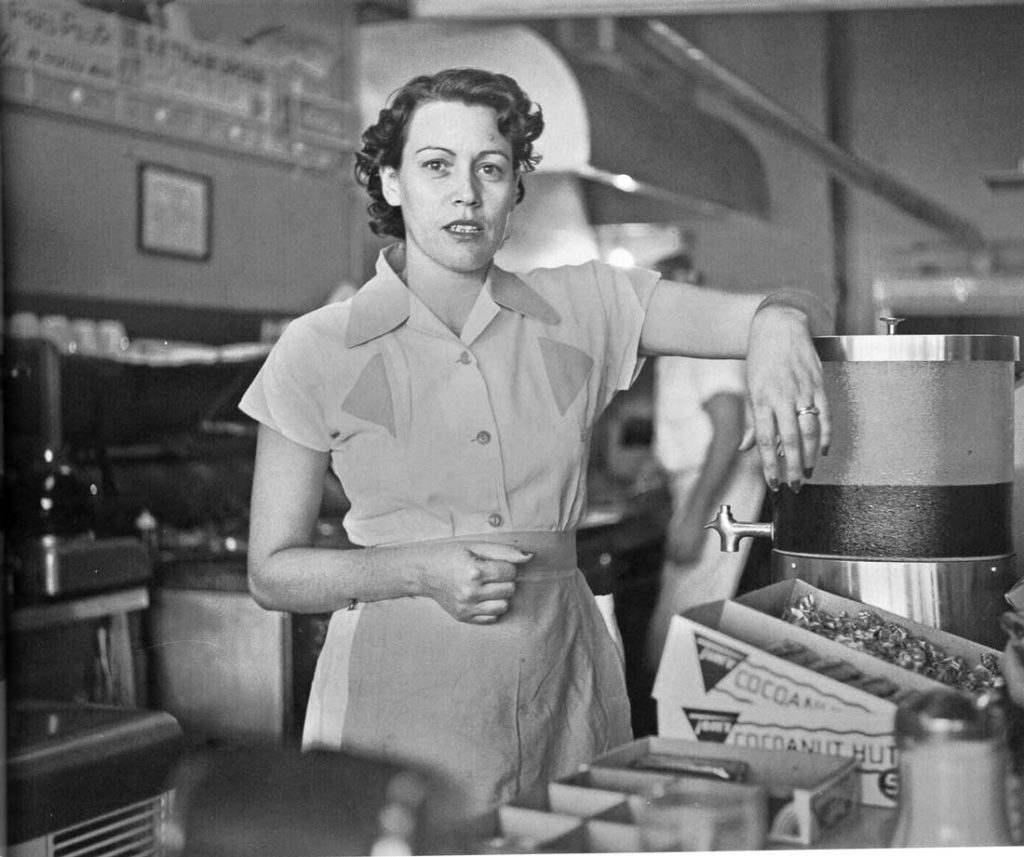Byrd III photographed Susie Morgan, a co-owner with husband Ernie Morgan of Ernie's Hamburger Stand, in 1955 in Fort Worth. The soft focus of the foreground and background, combined with Susie's crisp uniform and the placement of her face in front of stainless steel oven hood makes her pop off the page.