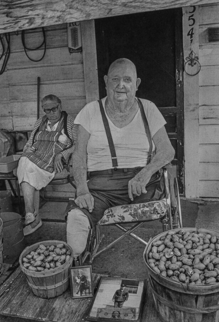 """In 1982, Byrd IV took this photo of a war veteran and pecan vendor named Mr. Brown, who sold pecans from his front porch located near the Williams' photo lab near Ripy and Jones streets. """"He was whole when I first met him,"""" Byrd IV writes in Proof. """"Diabetes kept whittling away at him until he disappeared. He was always friendly and lovable with a positive outlook on life. I would stop by occasionally and buy nuts from him so that I could photograph him, but his wife did not seem to approve. The exploitative nature of photographing strangers is always present and has only gotten worse with the digital tsunami. In my way of thinking, one must persevere because the photograph is for posterity and is bigger than him or me. We will both be dead soon enough, but the photograph will have an afterlife."""""""