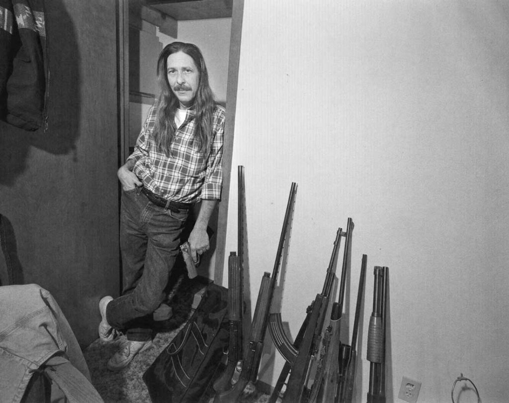 """A drug dealer or, as Byrd IV describes him, an """"addictive substance vendor,"""" poses with his tools of the trade –– a handgun and an array of shotguns and rifles. Check out the curved clip on the middle rifle and the hair and mustache (and tucked-in shirt) of the dapper dealer."""