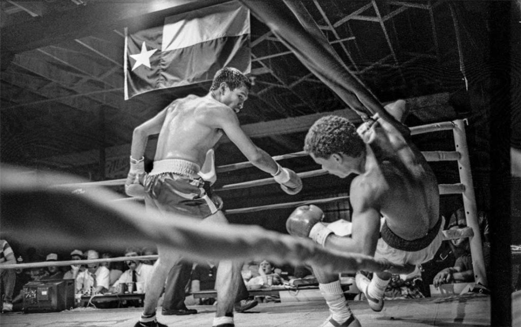 """A boxer scores a knockout at Gorman's Saturday Night Club fights, as photographed by Byrd IV in 1986. Gorman's was a popular gym near East Cannon Street in Fort Worth. Byrd IV's photograph is reminiscent of """"Dempsey & Firpo,"""" the famous painting by George Bellows that shows Luis Firpo knocking Jack Dempsey out of the ring in the first round of their fight in New York's Polo Grounds in 1923."""