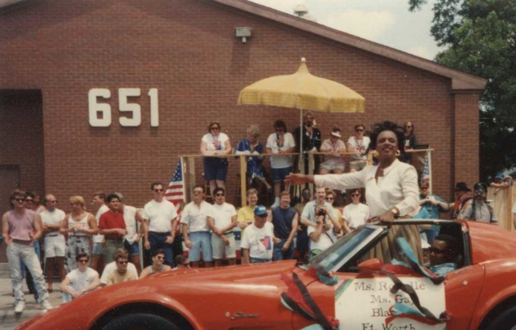 A Pride Parade shot from the '80s shows how the parade viewing stand was right in front of the 651. That's Ms. Ronelle, Ms. Gay Black Fort Worth, greeting onlookers while Raymond Gill announces in the background. From the collection of Todd Camp.