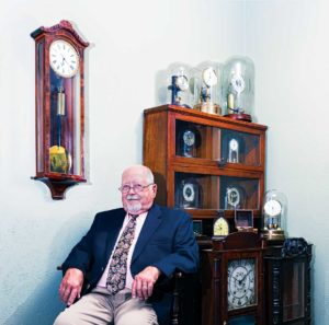 Bill Edwards sits surrounded by his unusually eclectic collection of very early 19th and 20th century windup, electrical, and wooden movement clocks. Photo by Chirag Sainju.