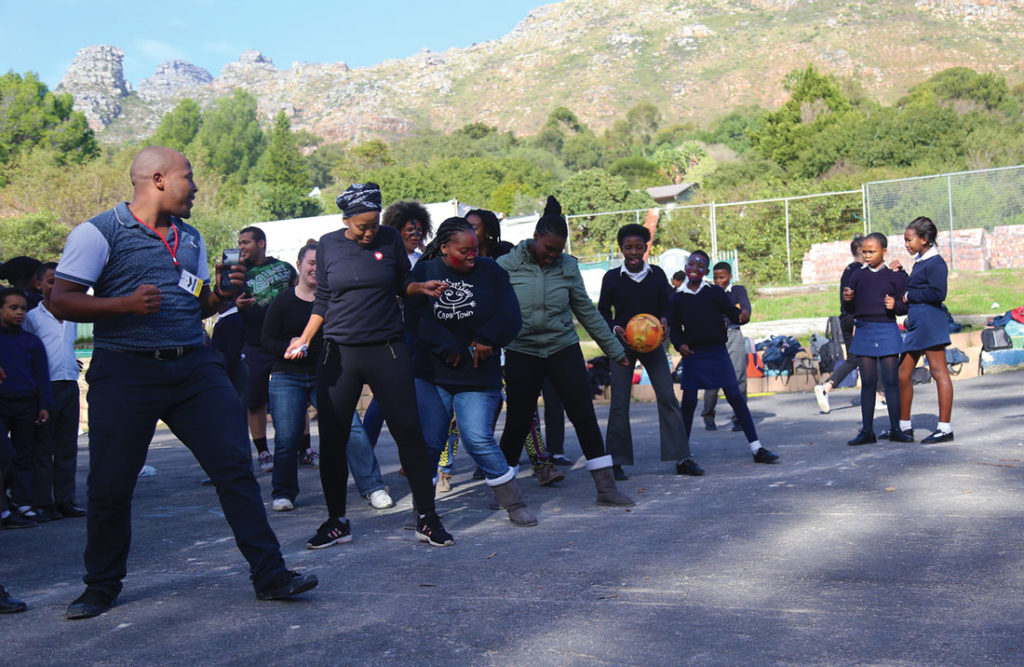 Lelo (far left) dances with students and volunteers during a Youth Day event. Photo by Diamon Garza.